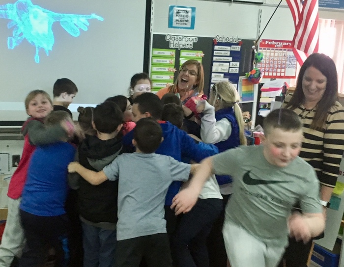 Ms. Sabourin getting hugs from students.